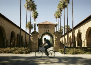 A man rides a bicycle in front of the sandstone buildings of Stanford University's Main Quad with palm trees in the background