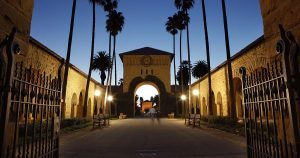 An evening view into Stanford University's Main Quad with arched sandstone buildings. Two people are walking away from the camera.