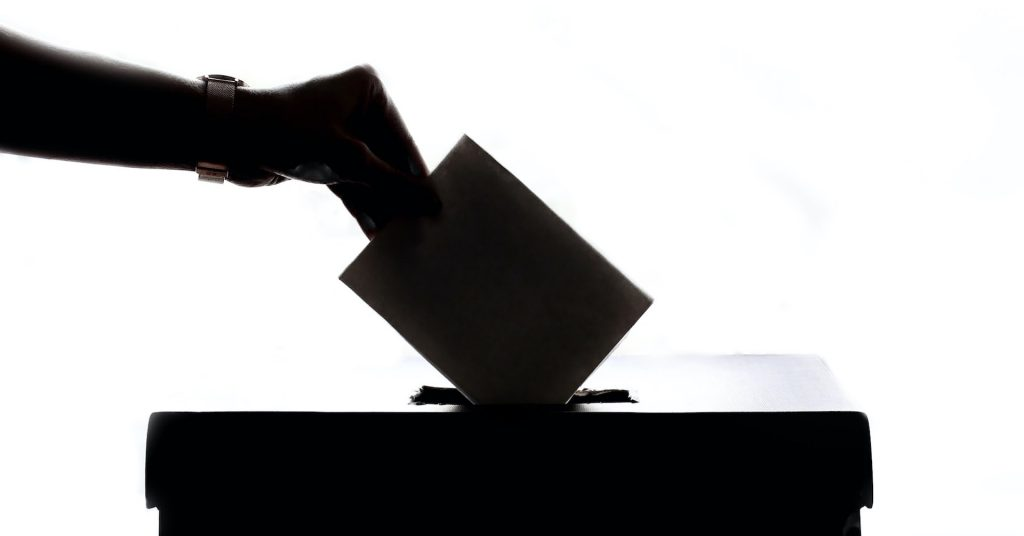 A hand places a piece of paper in a box. The objects are in black on a white background.